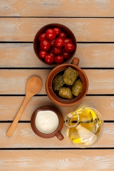 Top view dolma with yogurt olive oil and tomatoes on the wooden