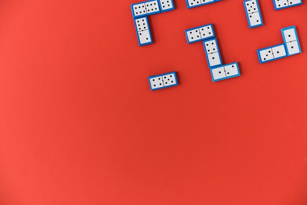 Top view domino pieces on red background