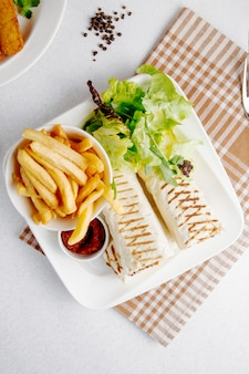 Top view of doner in lavash with french fries in the plate