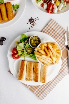 Top view of doner in lavash with fries and fresh salad on plate