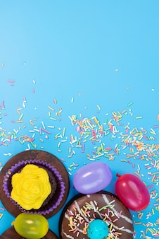 A top view donuts and brownies delicious and chocolate based along with candies on blue, candy cake biscuit color