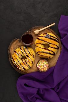 紫のティッシュと暗い周りの茶色の机の上のチョコレートとトップビュードーナツおいしいおいしい