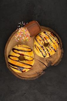 Вид сверху пончики сладкие вкусные вкуснятина с шоколадом на темном столе