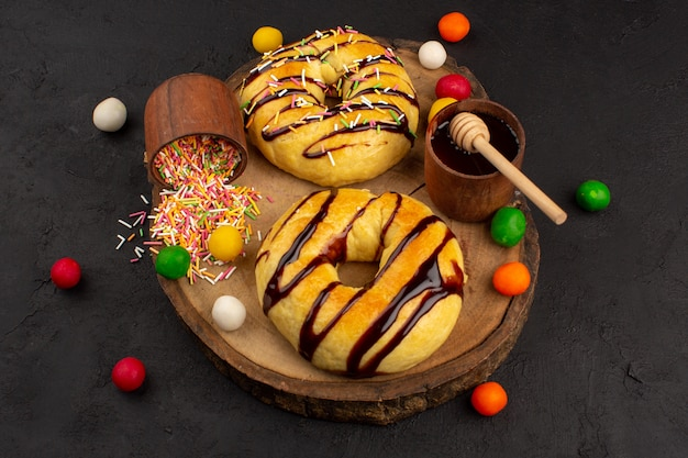 茶色の机と暗い色とりどりのキャンディーと並んでドーナツ甘いおいしいおいしいチョコ
