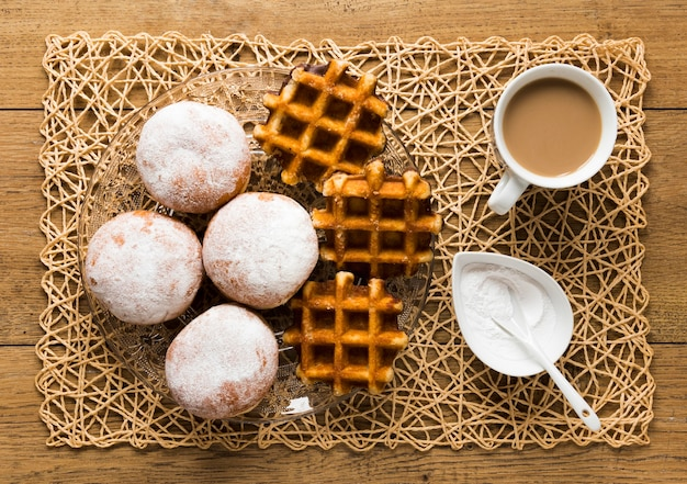 Top view of donuts with powdered sugar and waffles