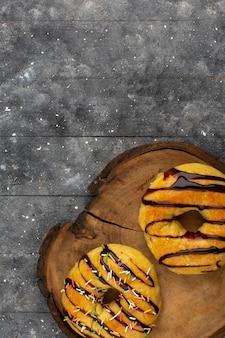 Vista dall'alto ciambelle deliziose con cioccolato sulla scrivania marrone e sfondo grigio