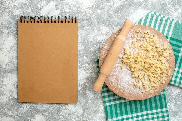 上面図生地とテーブルクロスの生地ボード上のめん棒灰色の背景のノートブック