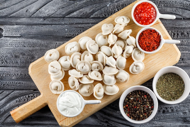 Top view dough on a cutting board with sauce, spices in bowls on gray wooden surface. horizontal