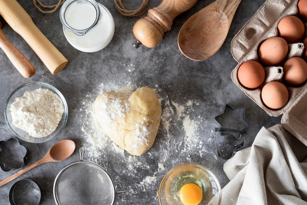 Вид сверху тесто на прилавке с мукой и яйцами