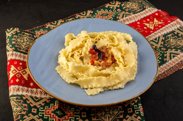 A top view dough pasta cooked tasty salted inside round blue plate on designed carpet and dark desk