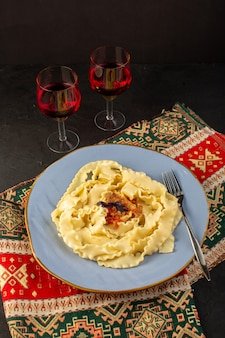 A top view dough pasta cooked tasty salted inside round blue plate with glasses of wine on designed carpet and dark desk