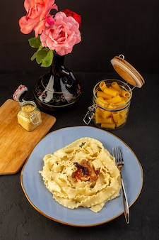 A top view dough pasta cooked tasty salted inside round blue plate with glasses of wine and flowers inside jug on designed carpet and dark desk italian meal cuisine