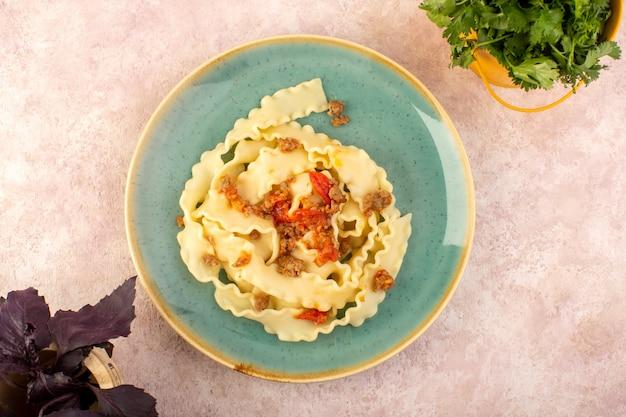 Una pasta di pasta vista dall'alto cucinata gustosa con verdure di carne e salata all'interno di un piatto verde rotondo con fiore sulla scrivania rosa