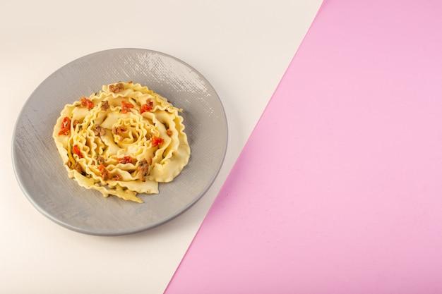 Una pasta di pasta vista dall'alto con carne cotta e verdure all'interno della lastra grigia su bianco-rosa