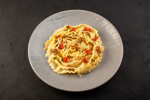 Una pasta di pasta vista dall'alto con verdure a fette cotte e carne all'interno della lastra grigia su oscurità