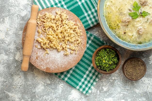 Vista dall'alto pasta e mattarello su tavola di pasta su tovaglia su sfondo grigio