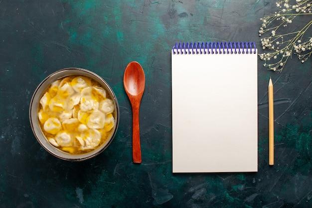 紺色の机の上の生地の中にひき肉が入った上面図の生地スープ材料スープ食品食事生地皿