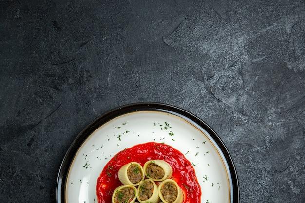 고기와 함께 상위 뷰 반죽은 어두운 회색 공간에 토마토 소스와 함께 반죽 조각을 슬라이스