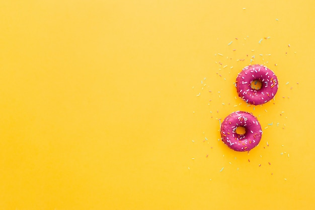 Top view of doughnut in pink icing on yellow background