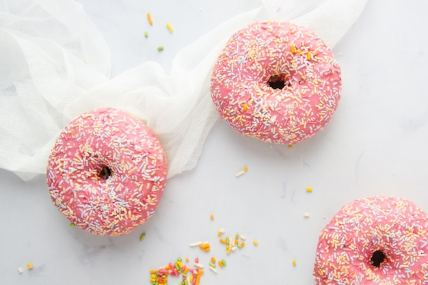 Top view of doughnuts with glazing and sprinkles