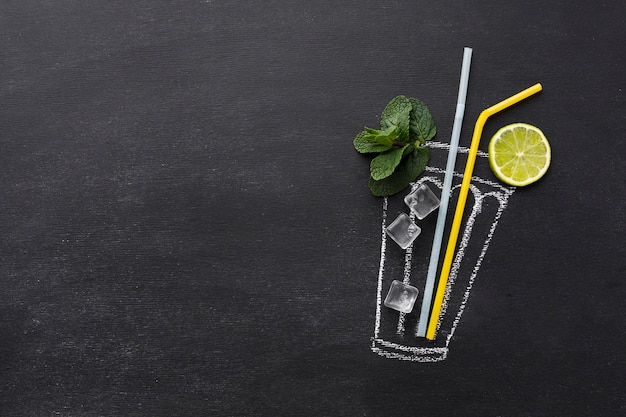 Top view of drawn cocktail glass with straws and lime