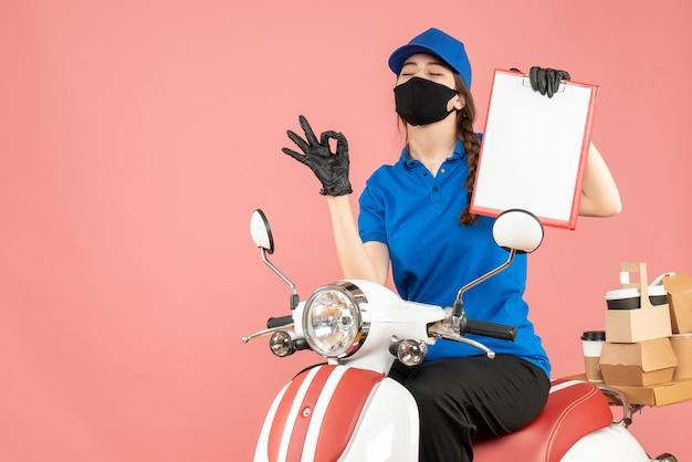Vista dall'alto della ragazza del corriere sognante che indossa maschera medica e guanti seduta su uno scooter con in mano un foglio di carta vuoto che consegna ordini su sfondo color pesca pastello