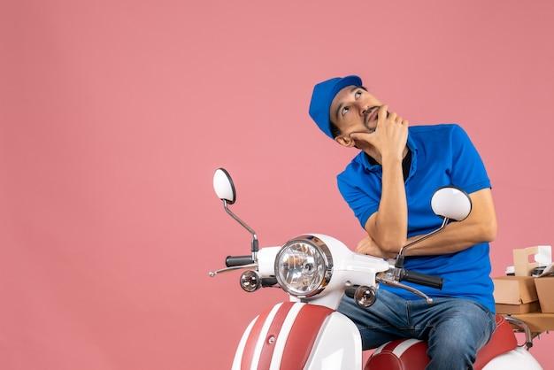Vista dall'alto del corriere da sogno che indossa un cappello seduto su uno scooter che consegna ordini su sfondo color pesca pastello