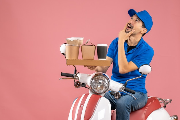 Top view of dreamy courier man wearing hat sitting on scooter on pastel peach background