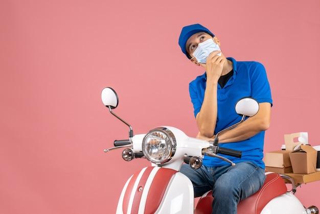 Vista dall'alto del ragazzo delle consegne sognante in maschera medica che indossa un cappello seduto su uno scooter su sfondo color pesca pastello