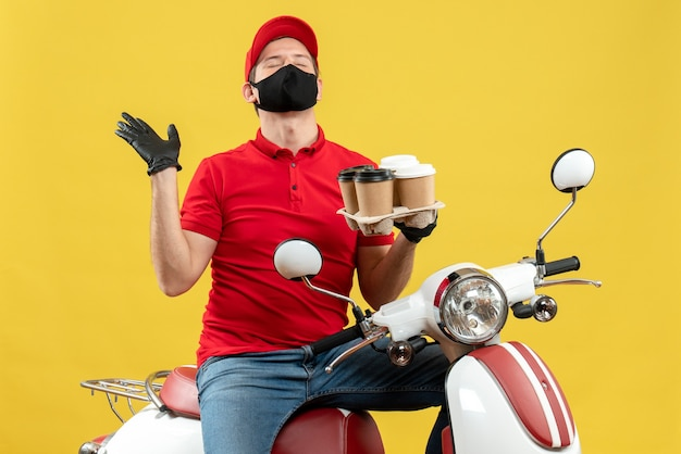 Top view of dreamy delivery man wearing uniform and hat gloves in medical mask sitting on scooter showing orders