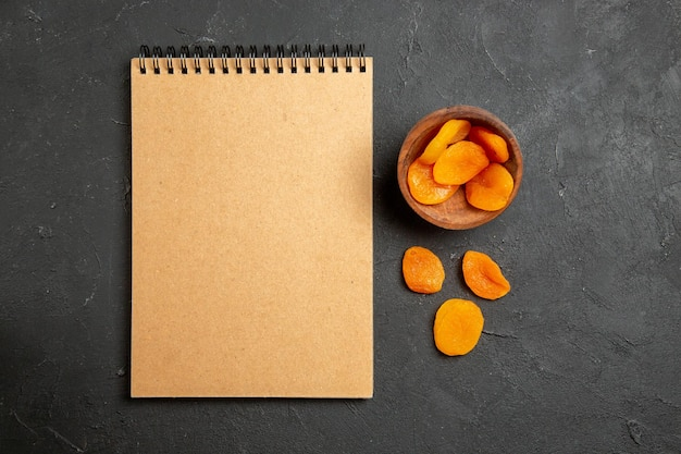 Top view dried apricot raisins with notepad on dark surface dry fruit raisin