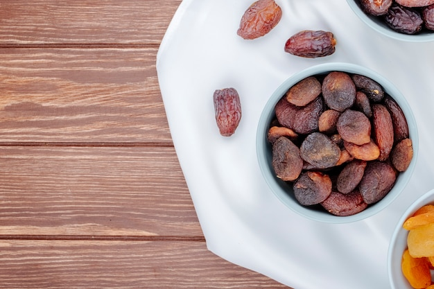 Top view of dried apricots in a bowl and with dried dates on wooden background with copy space