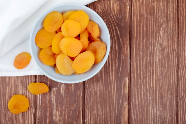 Top view of dried apricots in a white bowl on wooden background with copy space