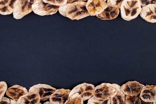 Top view of dried banana chips isolated on black background with copy space