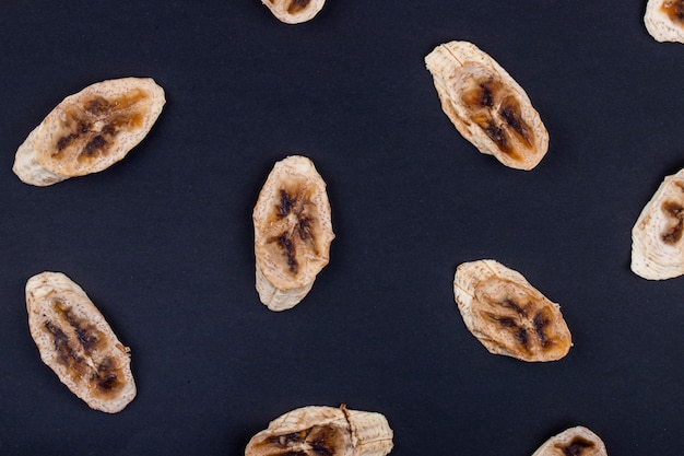 Top view of dried banana chips isolated on black background