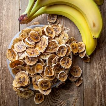 Вид сверху сушеные бананы в тарелку и свежие бананы на деревянный стол