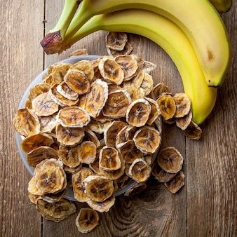 Top view dried bananas in plate and fresh bananas on wooden table