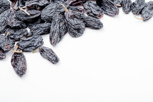 Top view of dried black raisins on white background with copy space