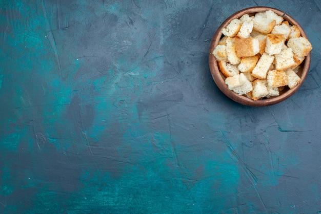 Vista dall'alto di fette biscottate di pane secco all'interno della ciotola marrone su fondente, fette biscottate di pane