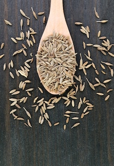 Top view of dried cumin seeds on wooden spoon with some scattered on the table