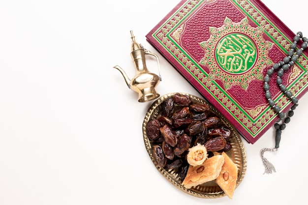 Top view of dried dates and quran with copy space