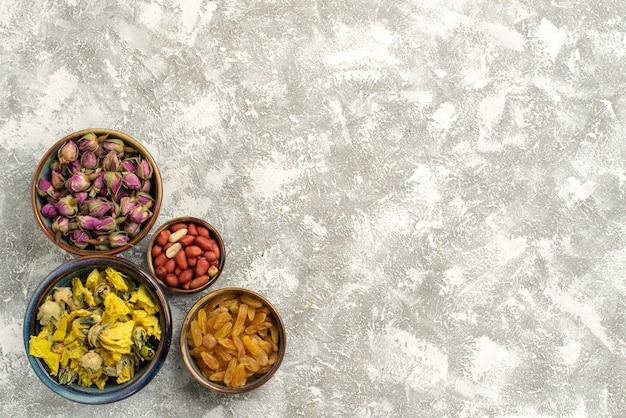 Vista dall'alto fiori secchi con noci e uvetta su sfondo bianco dado uva passa fiore pianta