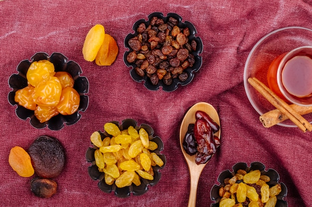 Top view of dried fruits cherry plums raisins apricots and dried dates in mini tart tins served with tea on dark red color background