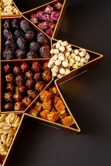A top view dried fruits and different nuts on the dark surface