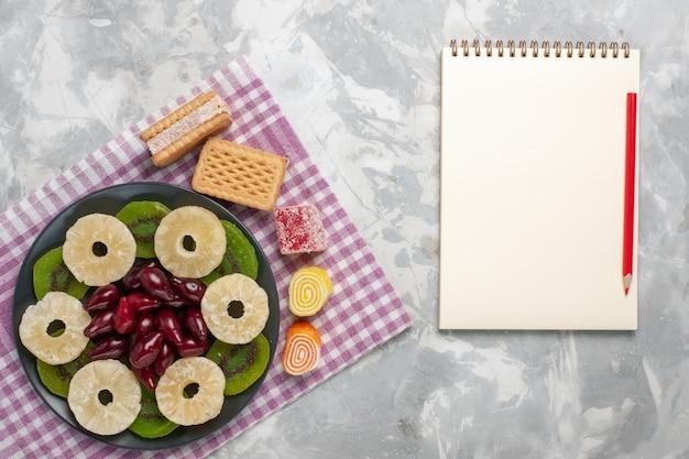 Вид сверху сушеные фрукты кольца ананаса кизилы вафли и ломтики киви на белом столе фрукты сухие сладкие сахар кислый