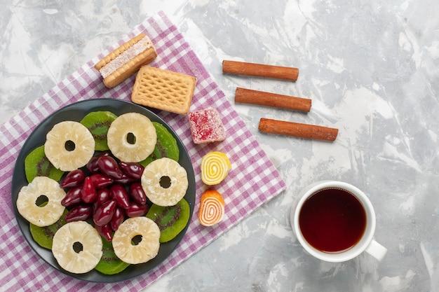 Вид сверху сушеные фрукты кольца ананаса кизилы вафли чашка чая и ломтики киви на белом столе фрукты сухие сладкие сахар кислый