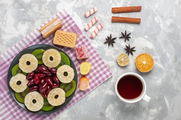Вид сверху сушеные фрукты кольца ананаса кизилы вафли чай и ломтики киви на белом столе фрукты сухие сладкие сахар кислый
