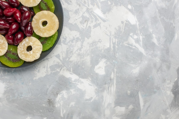 Vista dall'alto anelli di ananas frutta secca e fette di kiwi su sfondo bianco chiaro frutta secca dolce zucchero acido