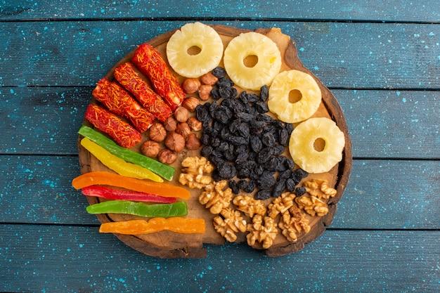 Vista dall'alto di anelli di ananas frutta secca, noci e torrone sulla superficie blu