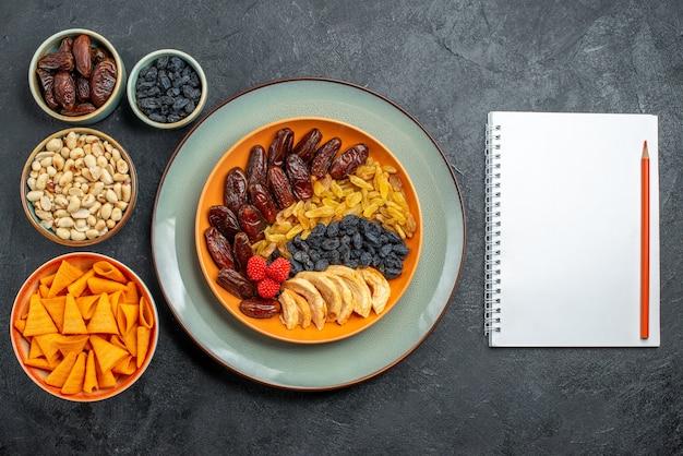 Vista dall'alto frutta secca con diverse uvetta e snack su uno spazio grigio